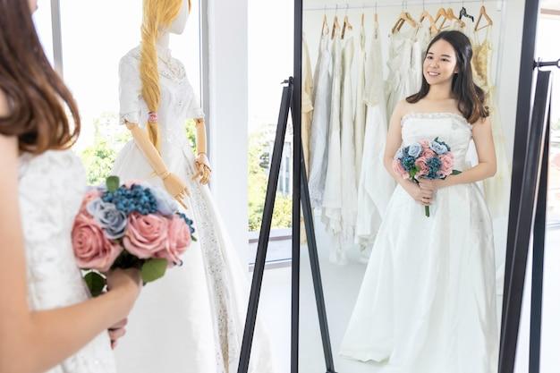 Azjatycka dama patrzy w lustro i uśmiecha się, wybierając suknie ślubne w sklepie.