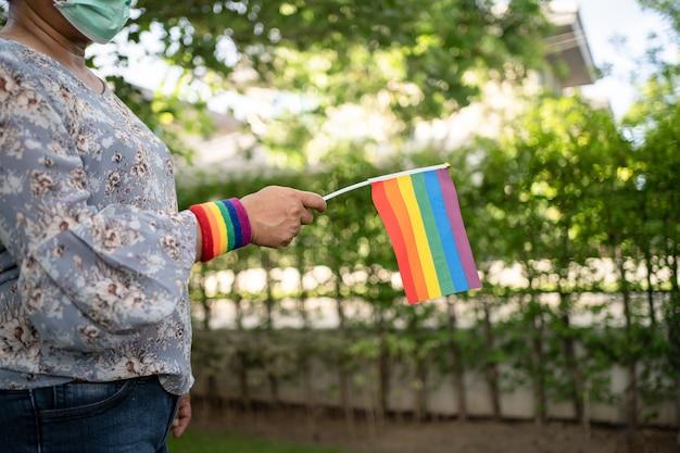 Azjatycka dama trzymająca tęczową flagę, symbol miesiąca dumy lgbt świętuje coroczne w czerwcu towarzyskie gejów, lesbijek, osób biseksualnych, transpłciowych, praw człowieka.