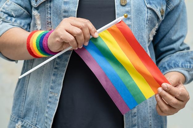 Azjatycka dama ubrana w niebieską dżinsową kurtkę lub dżinsową koszulę i trzymająca tęczową flagę, symbol miesiąca dumy lgbt, świętuje w czerwcu coroczne spotkania towarzyskie gejów, lesbijek, osób biseksualnych, transpłciowych, praw człowieka.