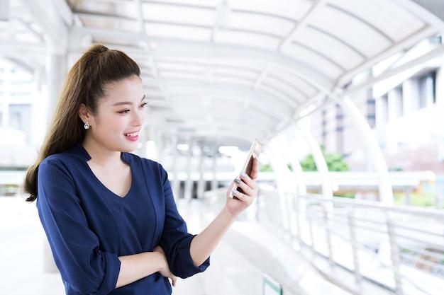 Azjatycka dama używa telefonu smartphone online social
