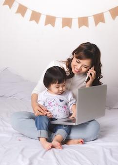 Azjatycka dama w klasycznym garniturze rozmawia przez telefon komórkowy i pracuje na laptopie w domu ze swoją córeczką.