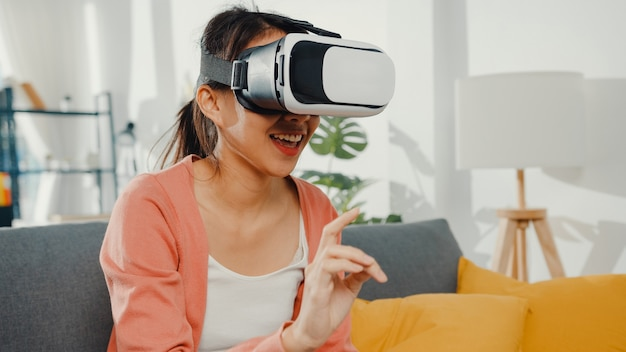 Azjatycka dama w okularach z zestawem słuchawkowym wirtualnej rzeczywistości gestykulując ręką siedzącą na kanapie w salonie w domu.