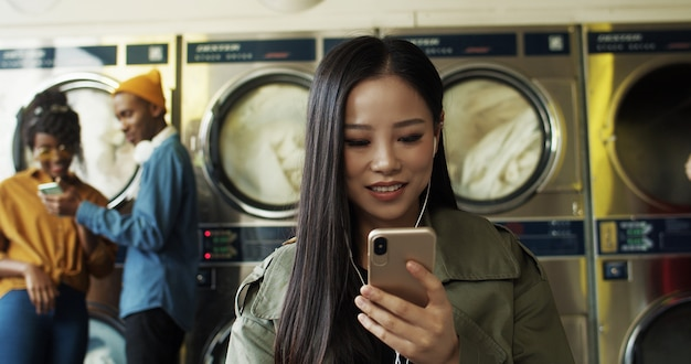 Azjatycka dosyć rozochocona kobieta ogląda wideo na smartphone w pralnianym usługowym pokoju w hełmofonach. piękna szczęśliwa dziewczyna słucha muzyka na telefonie i czeka ubrania czyści w pralni.