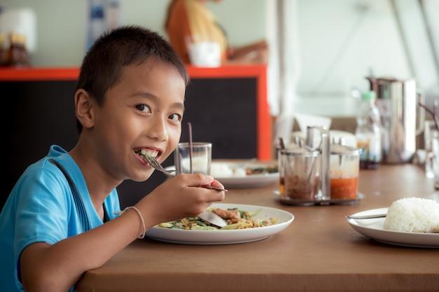 Azjatycka dziecko chłopiec je zdrowego jedzenie w stołówce lub bufecie.