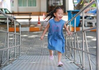 Azjatycka dziecko dziewczyna biega up metalu schodek