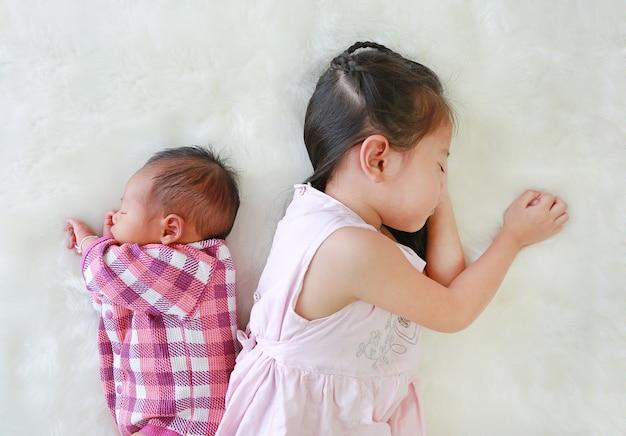 Azjatycka dziecko dziewczyna i dziecięca chłopiec dosypianie na białym futerkowym tle.