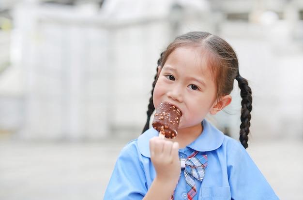 Azjatycka dziecko dziewczyna w mundurku szkolnym cieszy się łasowanie smakowitego czekoladowego waniliowego lody.