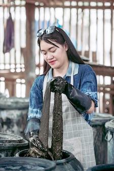 Azjatycka dziewczyna barwiąca tkanina z naturalnym indygo od sakon nakhon
