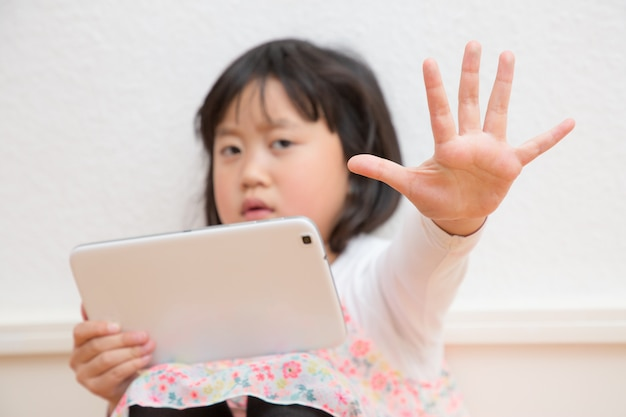 Azjatycka dziewczyna bawi tablet w salonie.