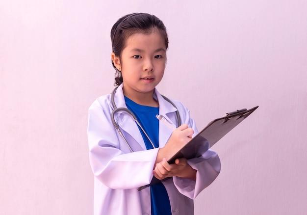 Azjatycka dziewczyna bawić się lekarkę z stetoskopem w rękach i pisze na schowku