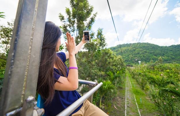 Azjatycka dziewczyna bierze selfie na widoku górskiego świetle