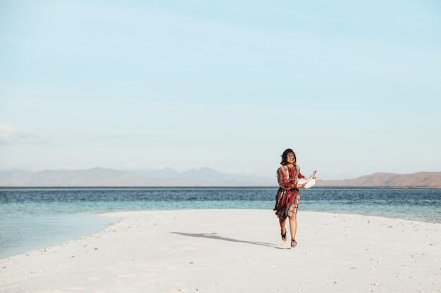 Azjatycka dziewczyna ciesząca się wakacjami i biegająca na białej, piaszczystej plaży