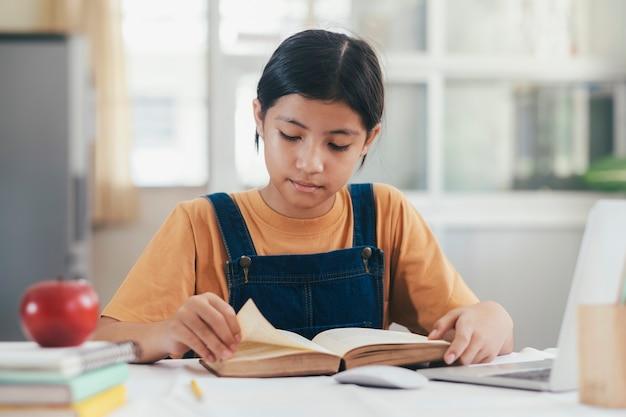Azjatycka dziewczyna czyta pracę domową i robi w jej domu