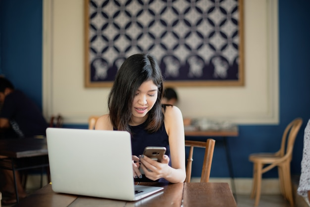 Azjatycka dziewczyna freelance używać smartphone podczas gdy pracujący z jej laptopem w coffeeshop.