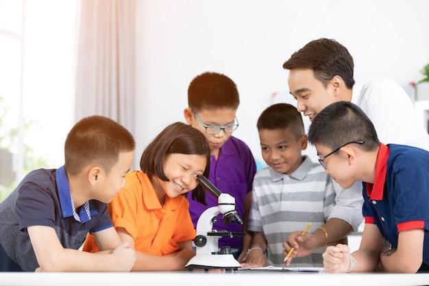 Azjatycka dziewczyna i chłopiec egzamininuje przygotowanie pod mikroskopem