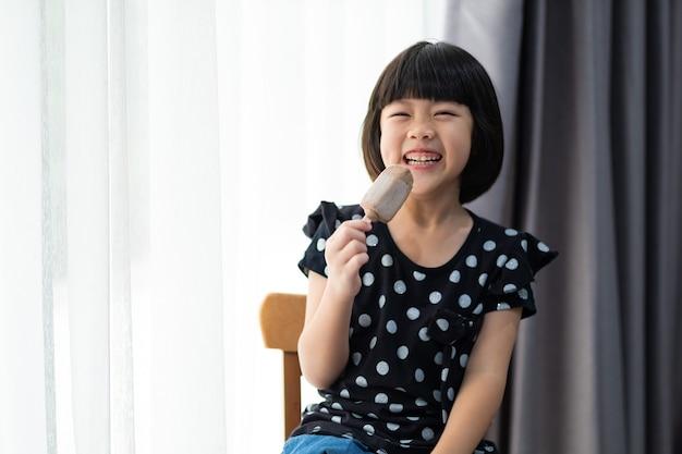 Azjatycka dziewczyna je lody z rozmytym tłem