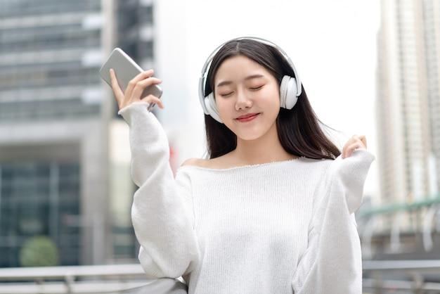 Azjatycka dziewczyna jest ubranym hełmofony i słucha streaming muzyka z oczami zamykającymi