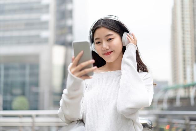 Azjatycka dziewczyna jest ubranym hełmofony słucha muzyka online z telefonu komórkowego
