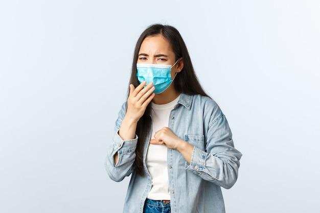 Azjatycka dziewczyna jest ubranym medyczną maskę i kaszle z pozytywnym testem koronawirusowym, jest chory na blokady
