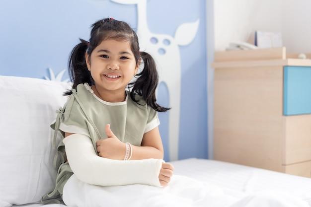 Azjatycka dziewczyna leczenie w szpitalu, leżąc na łóżku, boli ze złamaną ręką po operacji.