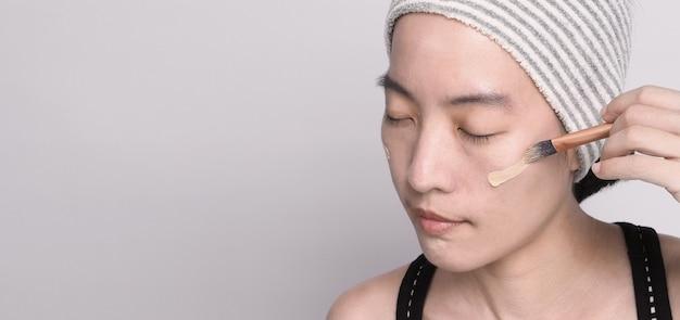 Azjatycka dziewczyna lub kobieta w wieku 40 lat, piękna twarz o japońskim wyglądzie, uzupełniona płynem do podkładu i pędzelkiem kosmetycznym na wrażliwej skórze, aby pomóc jej cerze wyglądać nieskazitelnie i bez retuszu.