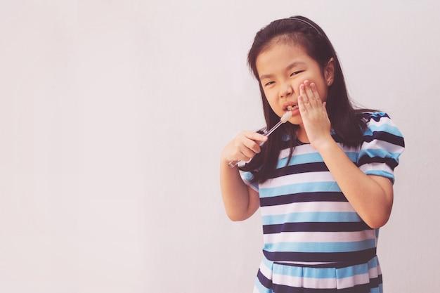 Azjatycka dziewczyna ma toothache trzyma szczoteczkę do zębów