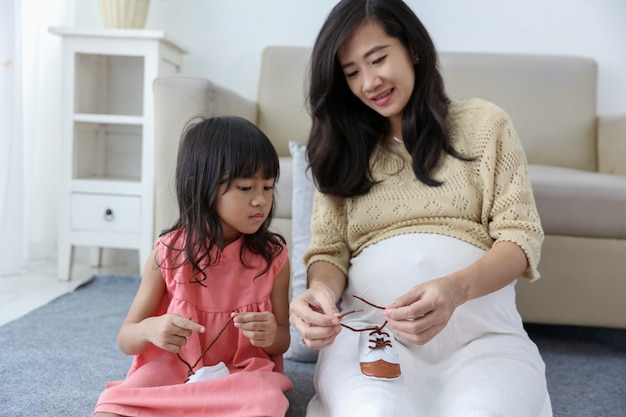 Azjatycka dziewczyna naprawia sznurowadła dziecka ze swoją ciężarną matką
