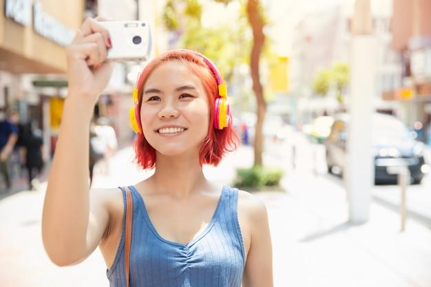 Azjatycka dziewczyna nastolatka szczęśliwy uśmiech podróżować z aparatem zrobić zdjęcie po mieście na świeżym powietrzu w sezonie letnim