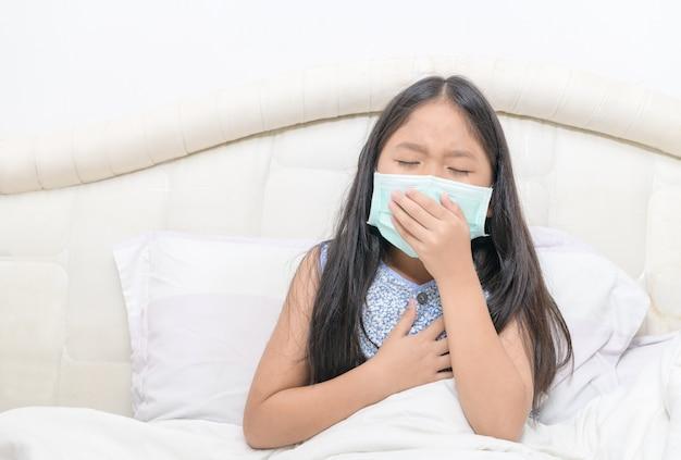 Azjatycka dziewczyna nosi higieniczną maskę kaszel i ból w klatce piersiowej,