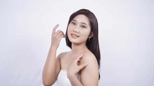 Azjatycka dziewczyna nosi makijaż pokazując jej uśmiechniętą twarz na białym tle