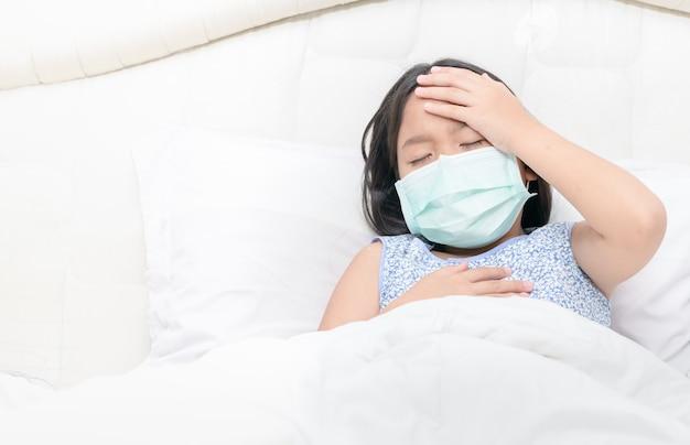 Azjatycka dziewczyna nosi maskę chirurgiczną ma wysoką gorączkę i ból głowy.