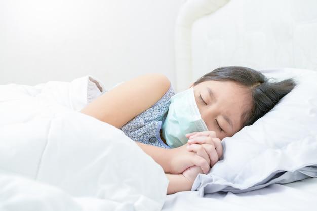 Azjatycka dziewczyna nosi maskę chirurgiczną spać na łóżku,