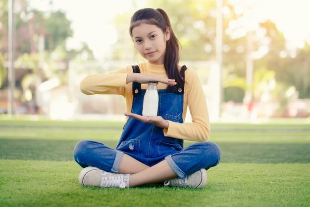Azjatycka dziewczyna pije pyszną butelkę mleka.