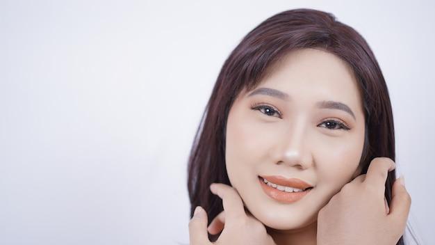 Azjatycka dziewczyna pokazująca twarz z makijażem na białym tle