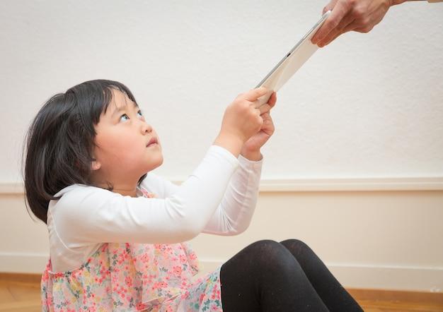 Azjatycka dziewczyna porywa tablet z ręki rodzica.