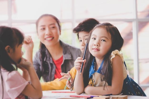 Azjatycka dziewczyna rysuje w dziecinie sztuki sala lekcyjnej