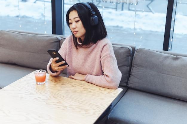 Azjatycka dziewczyna sama w mieście siedzi w kawiarni i słucha muzyki. ciesz się muzyką w miejscu publicznym