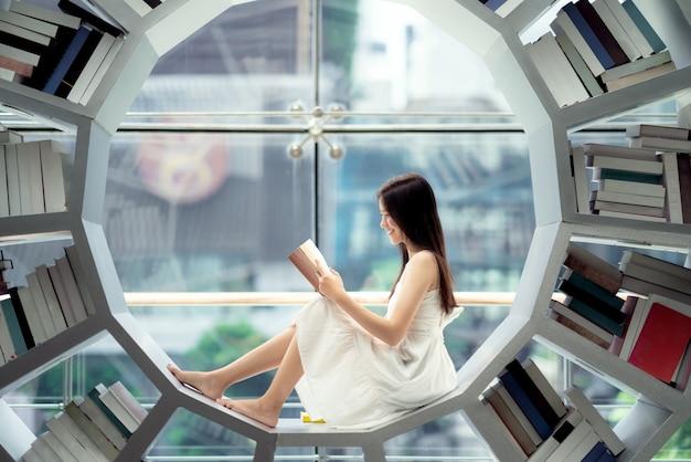 Azjatycka dziewczyna studentka czyta podręcznik w bibliotece na swoim uniwersytecie