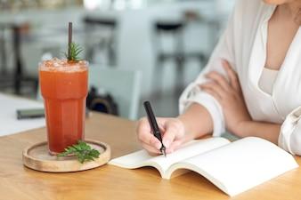 Azjatycka dziewczyna trzyma czarnego pióra writing w pustą książkę. Pamiętnik pisanie opowiadań