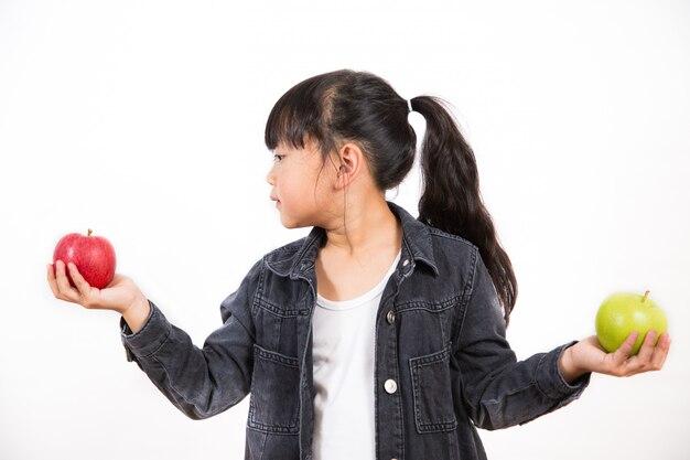 Azjatycka dziewczyna trzyma czerwonego i zielonego jabłka w jego ręce jest zdrowa i dobra dla bielu.
