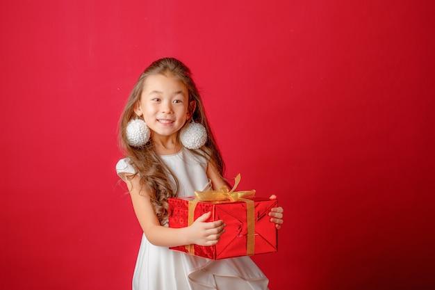 Azjatycka dziewczyna trzyma zabawki choinkowe na czerwonym tle, boże narodzenie