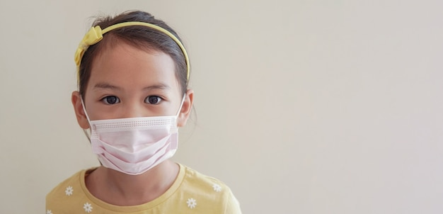 Azjatycka dziewczyna ubrana w medyczną maskę na twarz w celu ochrony wirusa koronawirusa, zanieczyszczenia powietrza i koncepcji zdrowia