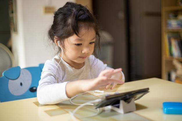 Azjatycka dziewczyna uczy się alfabetu w domu nowy normalny dystans społeczny koronawirusa covid19