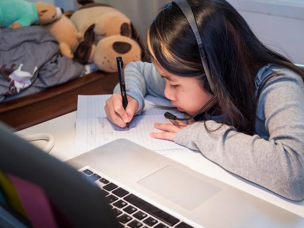 Azjatycka dziewczyna uczy się online z laptopem dziecko nosi zestaw słuchawkowy pisząc w zeszycie ucząc się za pomocą lekcji internetowych na kwarantannie uczennica uczy się przez internet lekcje online ze szkoły covid19