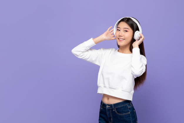 Azjatycka dziewczyna uśmiecha się hełmofony i dotyka podczas gdy słuchający muzyka i taniec
