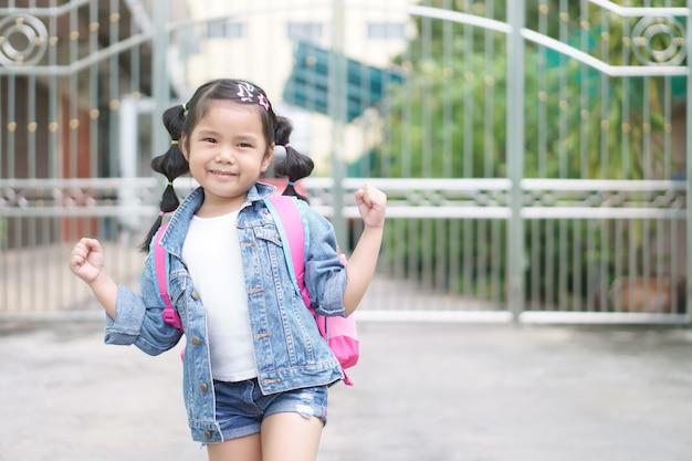 Azjatycka dziewczyna uśmiecha się i uczeń tornister na ramię z szczęśliwy i pokazuje garść dla silnych, zdrowych i pewnych siebie