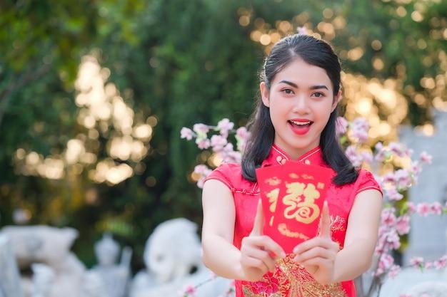 Azjatycka dziewczyna w czerwonej sukience chińskiego pochodzenia jest zadowolona z czerwonej koperty z dolarem
