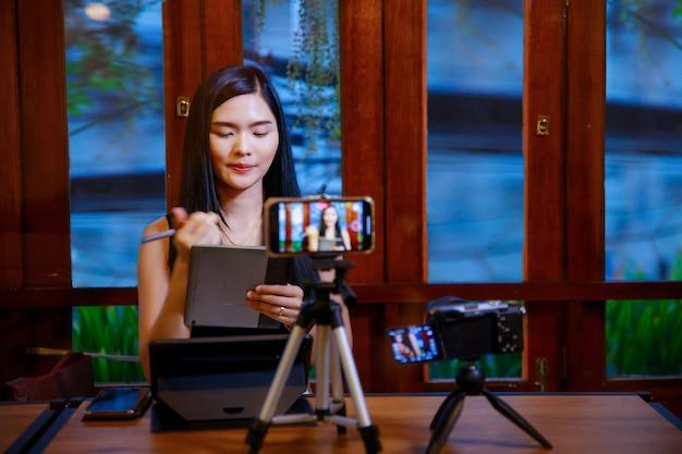Azjatycka dziewczyna w domu rozmawiająca przed kamerą na vlogowaniu