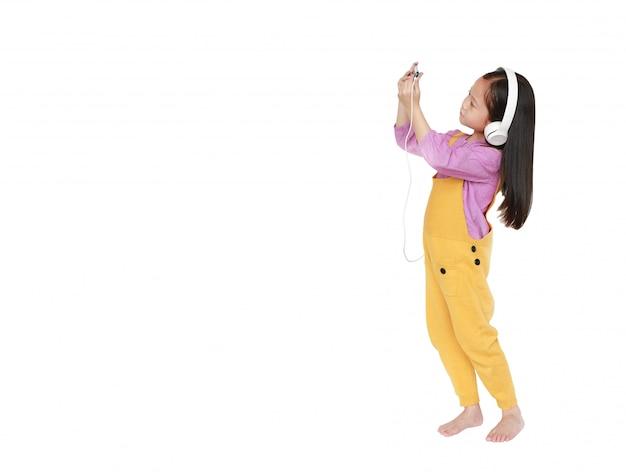 Azjatycka dziewczyna w dungarees z hełmofonami cieszy się słuchającą muzykę smartphone odizolowywającym na bielu.