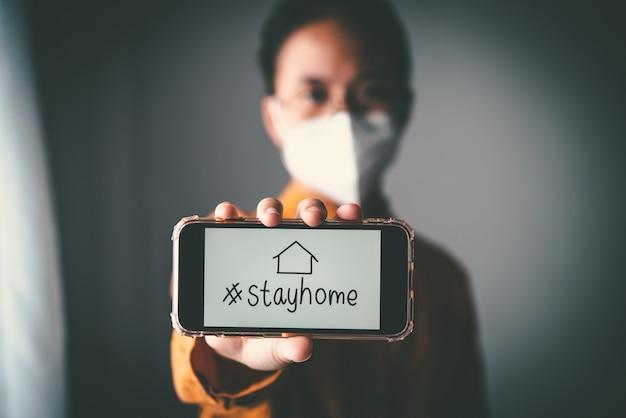 Azjatycka dziewczyna w okularach, w masce, trzymająca telefon z napisem #zostań w domu, jest znudzona koniecznością zatrzymania i leczenia choroby w domu. koncepcja kwarantanny domowej, zapobieganie covid-19